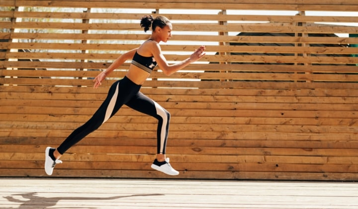 Kvinna med kompressions-tights som springer.