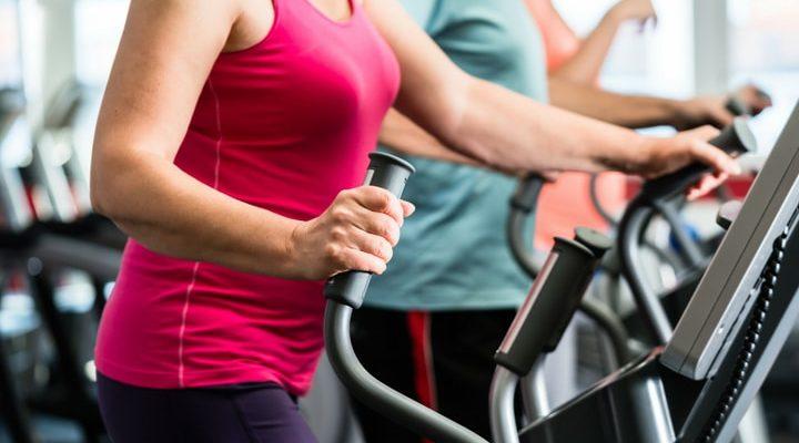 Kvinna med rosa tröja som tränar på en crosstrainer.