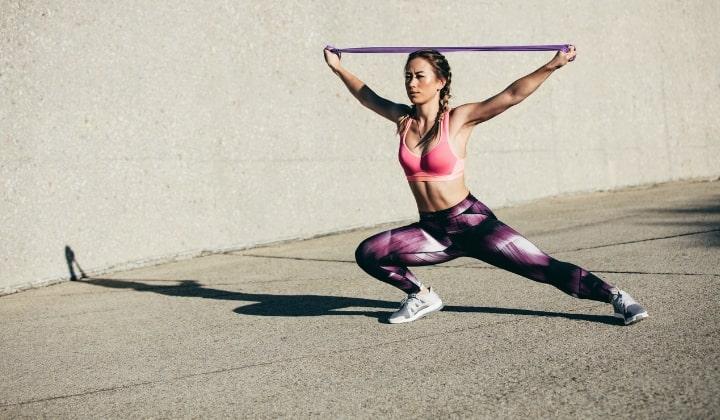 Kvinna står och tränar med ett gummiband.