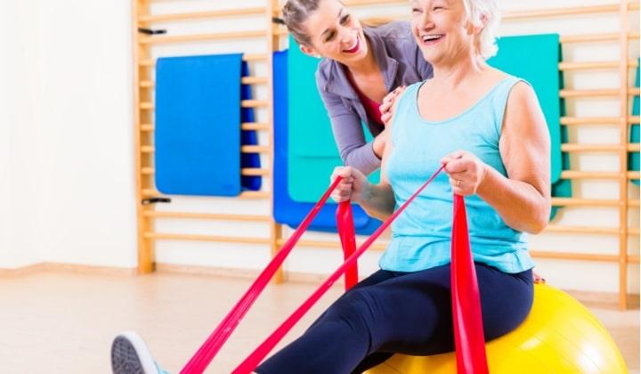 En äldre kvinna med en personlig tränare tränar med gummiband.