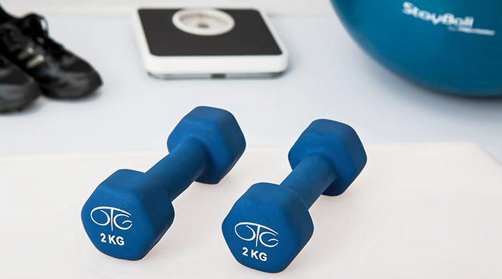 Två stycken blåa hantlar, bakom ligger en våg och en gymboll.