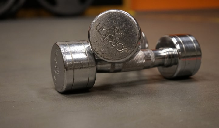Två stycken hantlar som ligger på varandra i rostfritt stål.