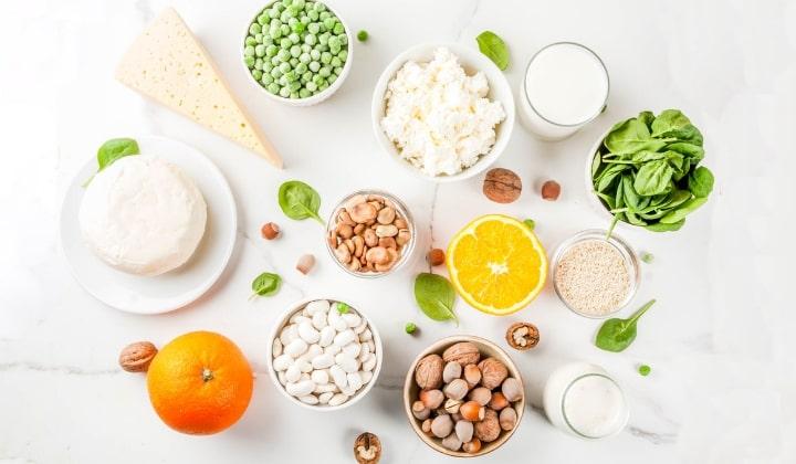 Olika skålar med livsmedel som innehåller kalcium på ett bord.