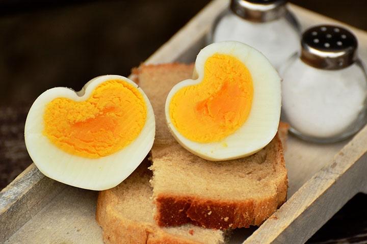 Två ägghalvor som ligger på två mackor.