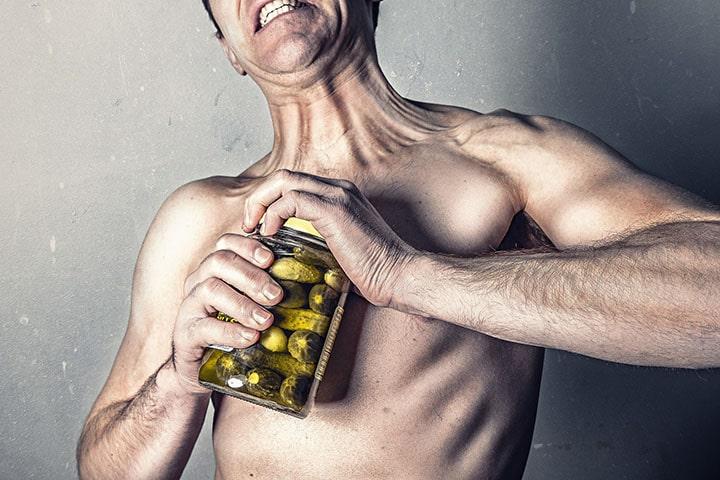 En man som försöker öppna en burk med pickles.