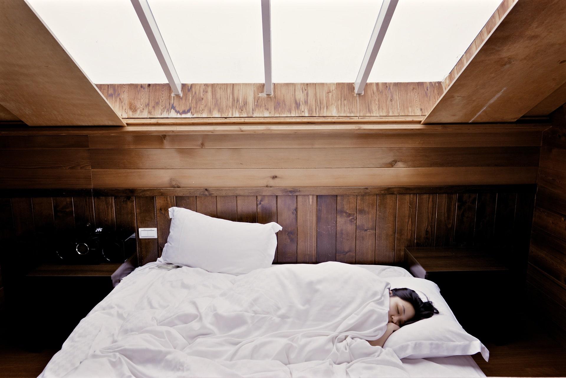 En kvinna i en säng som sover.