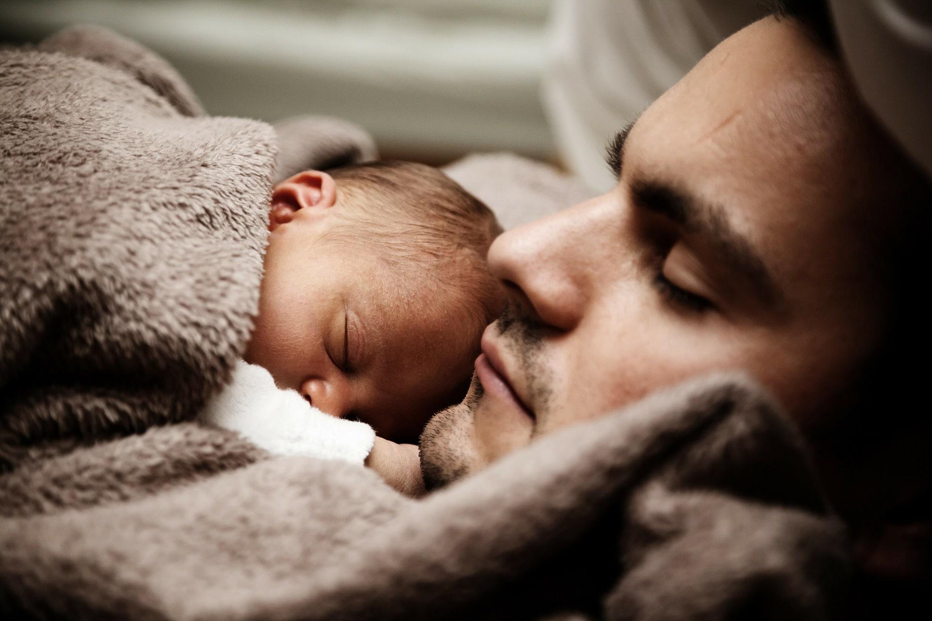 En pappa med en bebis på sig som sover.