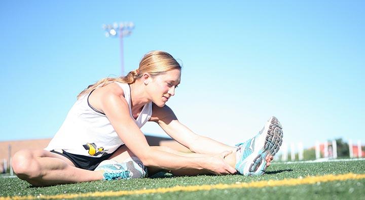 En tjej som sitter och stretchar på en idrottsplan.
